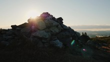 A Small Mound Of Stones Lies On The Top Of The Mountain. The Rays Of The Rising Sun Shine Because Of Him. Traditional Norwegian House For Trol