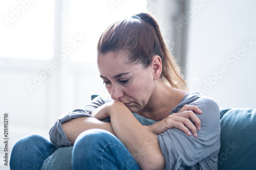 Fotografía Young attractive latin woman lying at home living room couch feeling sad tired and worried suffering depression in mental health, problems and broken heart concept