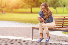 Young Woman Sitting On Bench A...