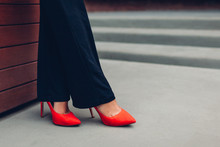 Young Businesswoman Wearing Red High Heeled Shoes. Stylish Classic Pumps. Closeup Of Female Legs.