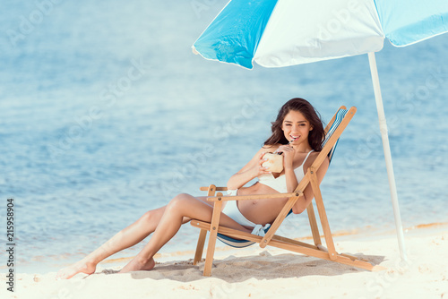 Fotografering happy young woman drinking cocktail in deck chair under sun umbrella near sea