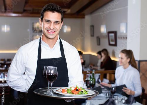 Staande foto Hoogte schaal Portrait of smiling waiter with serving tray meeting restaurant guests