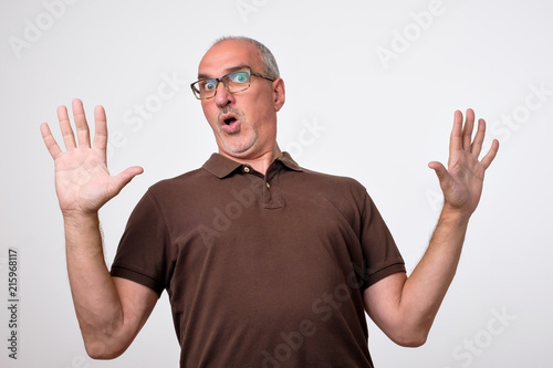 Man body language. I did not do it concept. Mature italian handsome man raising hands up. It is not my mistake