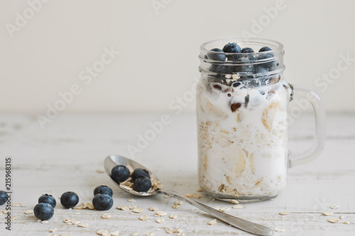 Overnight oats with whole grain cereal, fresh bluberries and coconut milk served with a spoon on wooden table. Healthy dessert for breakfast