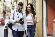 Smiling Tourist Couple With Cell Phone Walking In The City