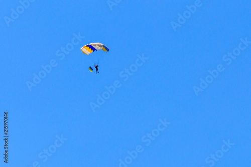 Foto op Canvas Luchtsport Parachutist carrying flag of Ukraine in blue clear sky