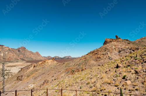 Spoed Foto op Canvas Blauwe jeans View of landscape of Teide National Park on Tenerife, Canarias islands, Spain. Yellow and black sand and distance view of mountains roads and volcano.