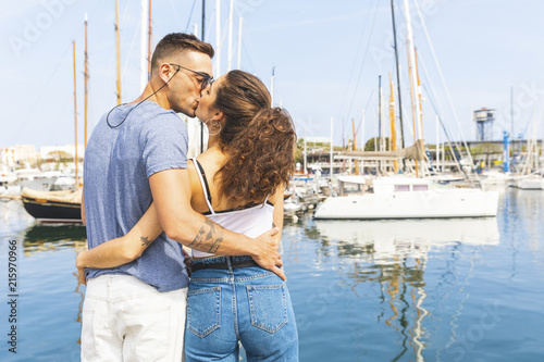 Back view of a young couple kissing at marina