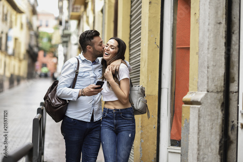 Happy tourist couple with cell phone walking in the city