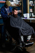 Hipster hairstyle concept. Hipster client getting haircut. Barber with hair clipper works on haircut of bearded guy barbershop background. Barber with clipper trimming hair on nape of client