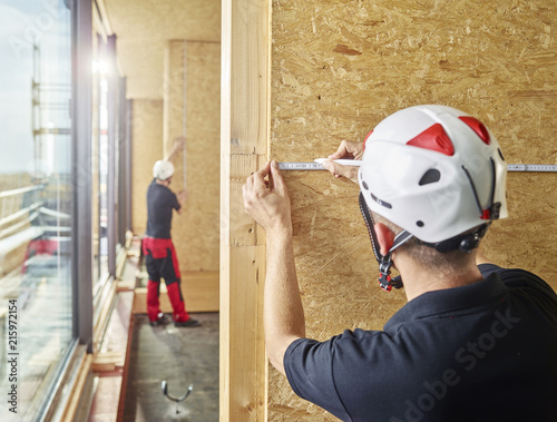 Worker with helmet marking flakeboard with pencil