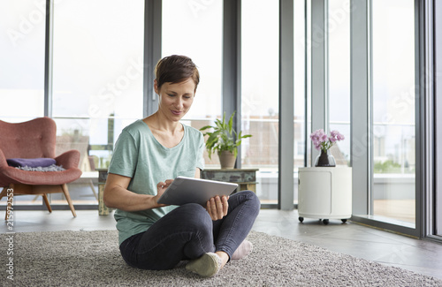 Woman sitting on the floor at home using tablet