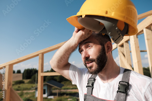 The man is a builder on the roof of a wooden frame house.