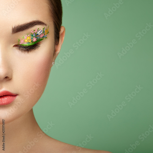 Obraz Young beautiful woman with flower makeup eyes. Spring makeup. Beauty fashion. Eyelashes. Cosmetic Eyeshadow. Make-up detail. Girl on green background - fototapety do salonu