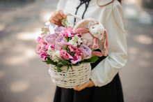 School Girl Holding A Cute Wicker Basket Full Of Bright Pink Flowers Decorated With A Toy