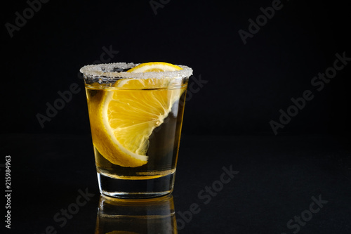 Fototapeta  A shot glass of tequila with salt and lime with black isolated background