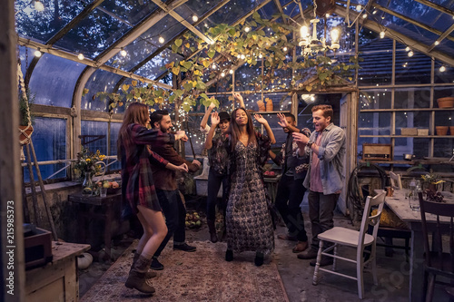 Young people having a party in greenhouse