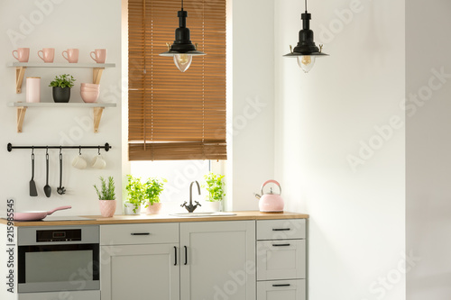 Fotografie, Obraz  Real photo of a bright kitchen interior with wooden counter, black lamps, white
