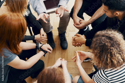 Fotografiet Close-up of hands of teenagers sitting in a circle during a support meeting