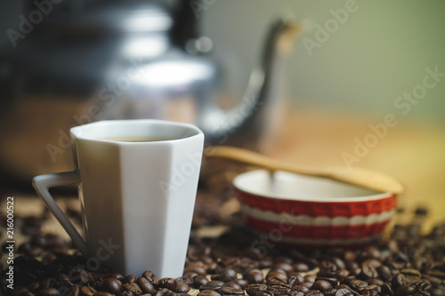 Fototapety, obrazy: Coffee cup and hot pot. Roasted coffee beans on brown wood background in morning.