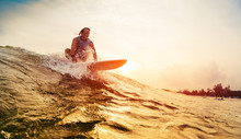 Young Surfer Rides The Wave During Sunset