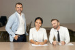 Smiling business people posing at desk in office. Businesspeople sitting, standing and looking at camera with blurred interior in background. Business team concept. Front view.