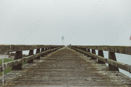 In de dag Poort Pier and lighthouse in the harbour of Deauville on a misty morning in Normandy, France. English channel seascape