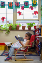 A Student Reading In A Kindergarten Classroom.