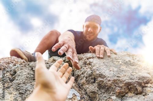 Fotografie, Obraz  Adventurers helping each other to climb
