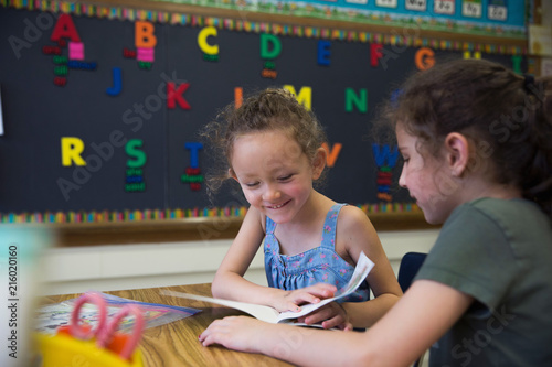 Two students reading a book in a kindergarten classroom.