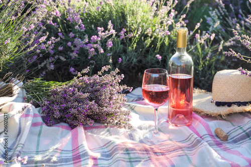 Bottle and glass of wine on blanket in lavender field