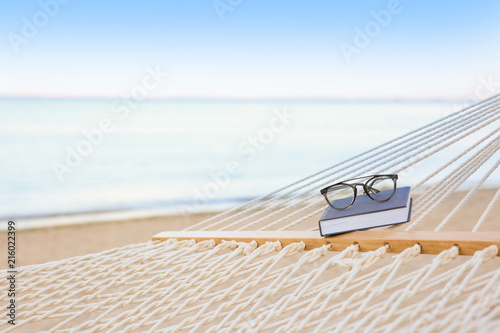Photo Comfortable hammock with book and glasses at seaside