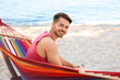 Young man sitting in colorful hammock at seaside
