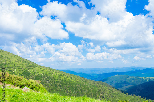 Summer landscape in mountains and the dark blue sky with clouds