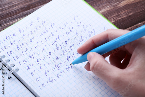 Female hand writing maths formulas in exercise book