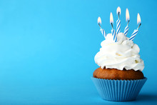 Tasty Cupcake With Candles On Blue Background