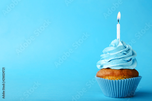 Fotografia  Tasty cupcake with candle on blue background
