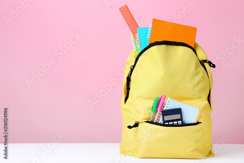 Obraz Yellow backpack with school supplies on pink background - fototapety do salonu