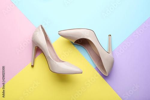 Fotografia Beige high heel shoes on colorful background