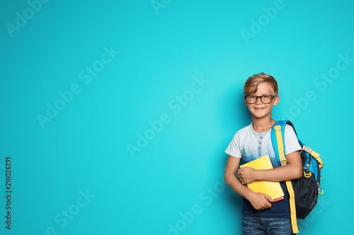 Obraz Little school child with backpack and copybooks on color background - fototapety do salonu