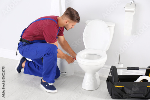 Young man working with toilet bowl in bathroom