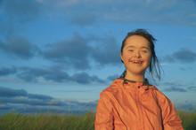 Portrait Of Little Girl Smiling On Background Of Blue Sky