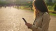 Woman with smartphone standing against sunlight