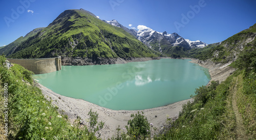 Poster Bergen Panorama view of Stausee Wasserfallboden, Hohe Tauern, Austria. Vibrant blue and green mountain lake with dam near Grossglokner. Mosserboden dam and alpine peaks in the background.