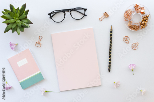 Photo Flat lay, top view office table desk workspace with office accessories including blank paper for lettering, notepad, glasses and plant on white background