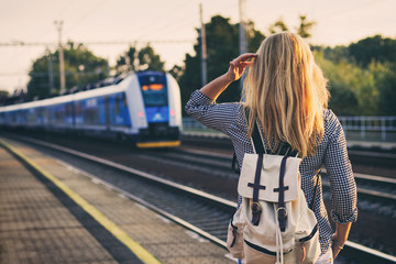 woman is looking at arriving train at a railway station