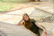Young girl lying on white wicker hammock and wearing khaki dress. Concept of summer vacations and resting on beach.