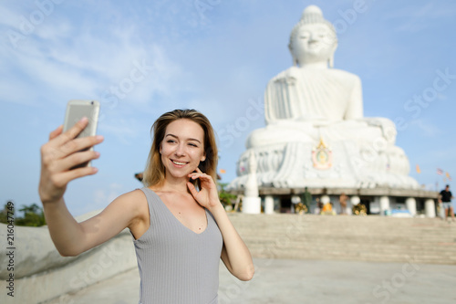 Young caucasian making selfie by smartphone near white statue of Buddha in Phuket. Concept of tourism in Thailand and landmarkd, buddhism religion.