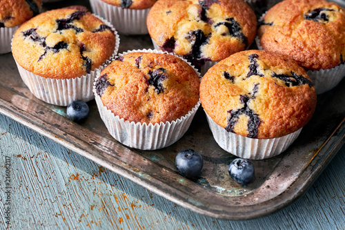 Photo Tasty blueberry muffins on old baking tray sitting on rustic wood, text space