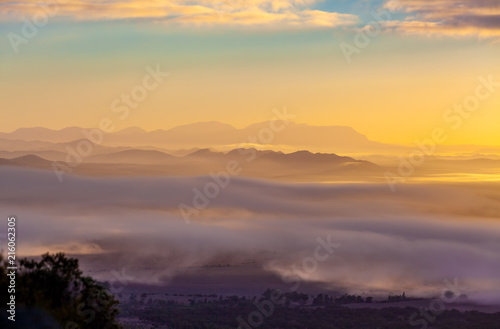 Poster Melon Mountain ridges protruding above low clouds at vivid sunset in Australia
